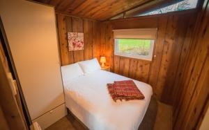 A bed or beds in a room at Timber Hill Self Catering Cedar Lodges