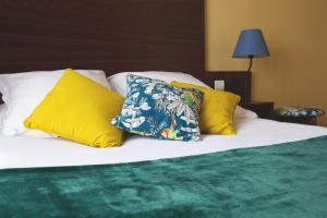 A bed or beds in a room at Hôtel Les Coutainvillaises