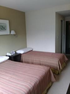 A bed or beds in a room at MIL810 Ushuaia Hotel