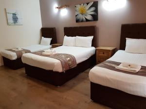A bed or beds in a room at Weaste Hotel