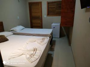 A bed or beds in a room at Pousada Farol