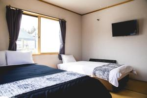 A bed or beds in a room at Hakuba Cortina Lodge