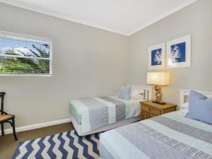 A bed or beds in a room at Barrenjoey at Iluka Resort Apartments