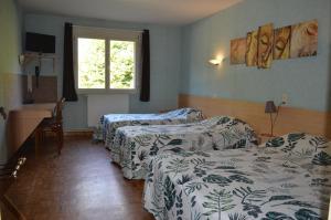 A bed or beds in a room at Hôtel De Courteilles