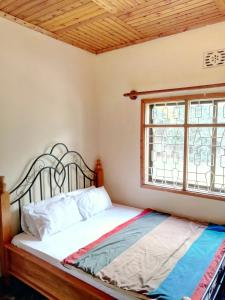 A bed or beds in a room at Mazzola Safari House & Backpacking