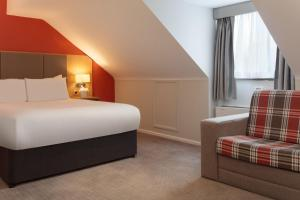 A bed or beds in a room at Oxford Witney Hotel