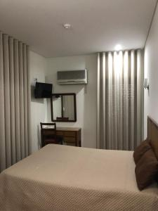 A bed or beds in a room at Ze da Rampa Hotel