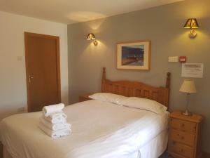 A bed or beds in a room at The Gardeners Country Inn