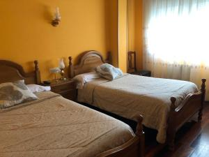 A bed or beds in a room at Hostal Galicia