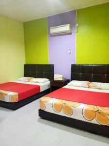 A bed or beds in a room at Taman negara rainbow guest house