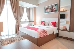 A bed or beds in a room at OYO Flagship 755 Appartel Grand Dhika City