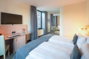 A bed or beds in a room at IntercityHotel Hamburg Hauptbahnhof
