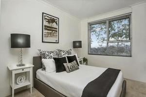 A bed or beds in a room at Leafy Apartment in Lane Cove - JANET