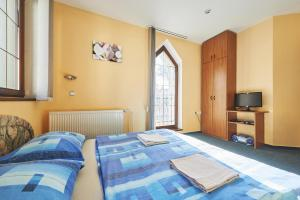 A bed or beds in a room at Penzion Vila Milica