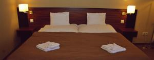 A bed or beds in a room at Fiáker Panzió