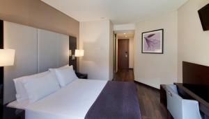 Uma cama ou camas num quarto em TURIM Luxe Hotel