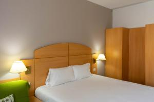 A bed or beds in a room at Campanile Madrid Alcalá de Henares