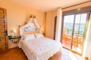 A bed or beds in a room at Hotel Rural Sierra Tejeda