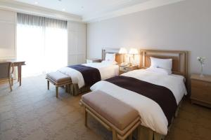 A bed or beds in a room at Okura Akademia Park Hotel