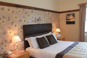 A bed or beds in a room at Silver Tassie Hotel & Spa