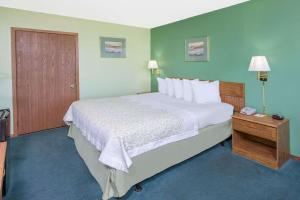 A bed or beds in a room at Days Inn by Wyndham Mountain Grove