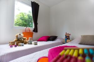 A bed or beds in a room at Camping Officiel Siblu Le Bois Dormant