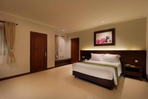 A bed or beds in a room at Adi Dharma Cottages