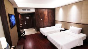 A bed or beds in a room at The Arista Hotel Palembang