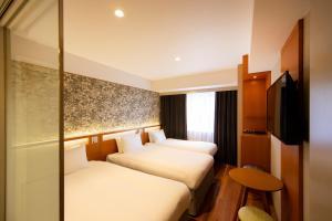A bed or beds in a room at karaksa hotel grande Shin-Osaka Tower