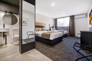 A bed or beds in a room at CBD Motor Inn