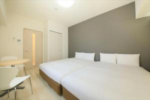 A bed or beds in a room at BAY HOTEL Urayasu-ekimae