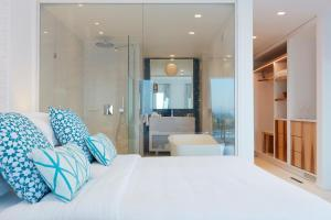A bed or beds in a room at Myconian Ambassador Relais & Chateaux