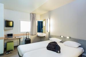 A bed or beds in a room at ibis budget Paris Porte De Montmartre