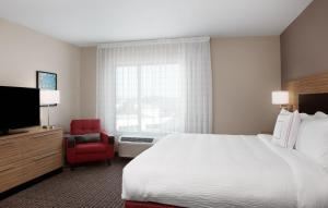 A bed or beds in a room at TownePlace Suites by Marriott Orlando Theme Parks/Lake Buena Vista