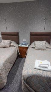 A bed or beds in a room at Grove House Hotel