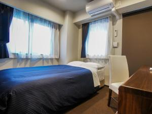 A bed or beds in a room at Hotel Livemax Umeda Doyama