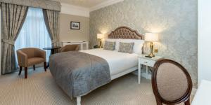 A bed or beds in a room at Stauntons on the Green Hotel