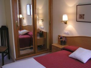 A bed or beds in a room at Hotel La Brañina