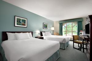 A bed or beds in a room at Harrison Lake Hotel