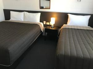 A bed or beds in a room at Mandalay Motel