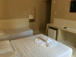 A bed or beds in a room at Hotel Coqueiral