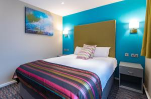A bed or beds in a room at The Victoria Hotel Manchester by Compass Hospitality