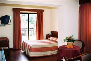 A bed or beds in a room at Ekali Hotel
