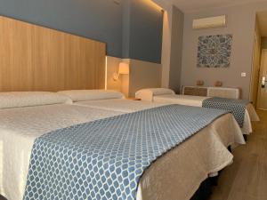 Säng eller sängar i ett rum på Hotel Puerta del Mar