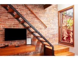 A television and/or entertainment center at Renovated heritage terrace in unbeatable location
