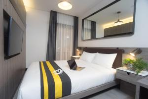 A bed or beds in a room at Rooms Inc Hotel Pemuda