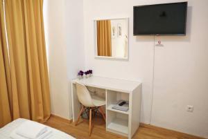 Una televisión o centro de entretenimiento en Hotel Delfin