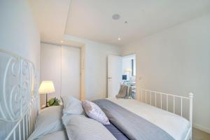 A bed or beds in a room at A Cozy & Stylish 2BR CBD Apt Near Southern Cross