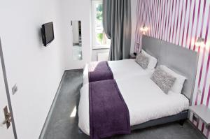A bed or beds in a room at Hotel Nougier