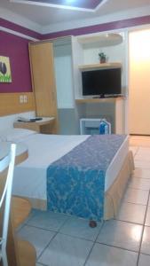 A television and/or entertainment center at Raio de Sol Praia Hotel